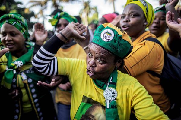 Un grupo de personas vestidas con los colores del Congreso Nacional Africano cantan y bailan a las puertas del Tribunal Supremo durante una manifestación en apoyo del ex presidente Jacob Zuma.