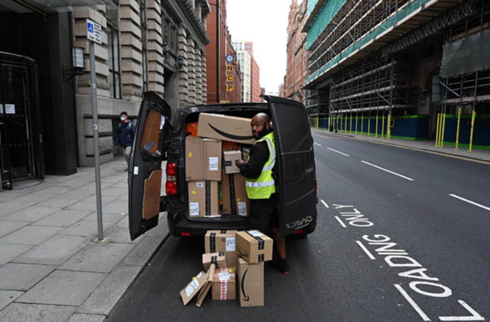 Un repartidor de Amazon posa junto a su furgoneta con el maletero repleto de paquetes. (AFP)